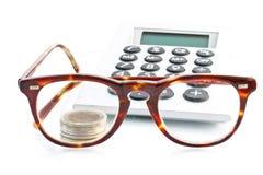 Dinero, calculadora y vidrios Fotos de archivo libres de regalías
