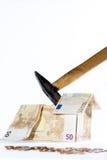 Dinero-casa hecha de billetes de banco, de monedas y del martillo Fotografía de archivo libre de regalías