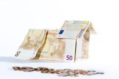 Dinero-casa hecha de billetes de banco y de monedas Imagenes de archivo