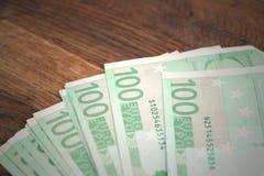 Dinero cientos euros en la tabla de madera imagenes de archivo