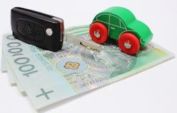 Dinero, coche verde del juguete y vehículo de la llave Fondo blanco Foto de archivo