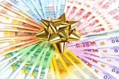 Dinero como regalo cinta de oro en fondo euro de los billetes de banco Imagen de archivo