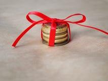 Dinero como regalo de la Navidad, monedas en una tabla con el arco rojo fotos de archivo