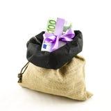 Dinero con el arco rosado en bolso del yute Fotografía de archivo libre de regalías