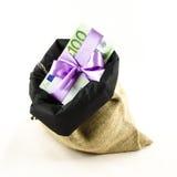 Dinero con el arco rosado en bolso del yute Imagen de archivo libre de regalías