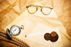 Dinero con el reloj, los vidrios y la cuerda en sobre Imagen de archivo