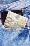 Dinero con el teléfono móvil en bolsillo de los vaqueros Cashless o efectivo que paga concepto que hace compras imágenes de archivo libres de regalías