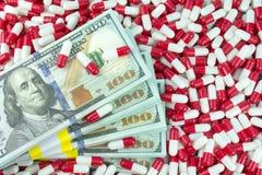 Dinero con las píldoras farmacéuticas de la medicina imagen de archivo