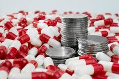 Dinero con las p?ldoras Coste de drogas fotografía de archivo