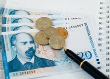 Dinero con una pluma y algunas monedas Imágenes de archivo libres de regalías