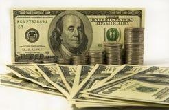Dinero Dólares y pila de monedas en el fondo blanco Concepto del dinero del ahorro Asunto cada vez mayor Confianza en el futuro Fotos de archivo libres de regalías