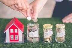Dinero de ahorro de la familia que pone las monedas en el banco de cristal, planes de los ahorros para contener, concepto financi imagen de archivo libre de regalías