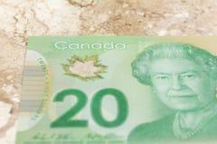 Dinero de Canadá: Dólares canadienses Primer en la tabla de mármol imágenes de archivo libres de regalías