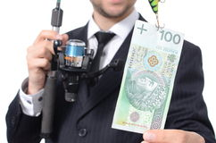 Dinero de cogida del hombre de negocios con la caña de pescar Fotografía de archivo libre de regalías