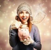 Dinero de depósito feliz de la mujer joven en su hucha Imagen de archivo libre de regalías