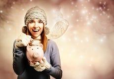 Dinero de depósito feliz de la mujer joven en su hucha Fotos de archivo libres de regalías