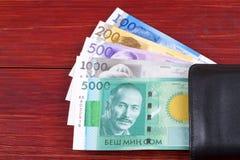 Dinero de Kirguistán en la cartera negra imagen de archivo