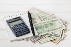 Dinero de la calculadora, del cuaderno, de la pluma y del efectivo en la tabla blanca Imagen de archivo