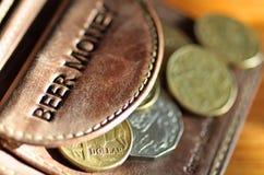 Dinero de la cerveza. Monedas australianas fuera de una carpeta de cuero Imagen de archivo libre de regalías