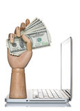 Dinero de la explotación agrícola de la mano del maniquí en una computadora portátil del ordenador Imagen de archivo libre de regalías