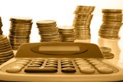 Dinero de la moneda en pilas con la calculadora foto de archivo