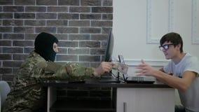 Dinero de la paga del terrorista al pirata informático de ordenador, mano a mano, sentándose metrajes