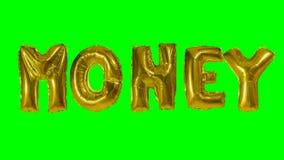 Dinero de la palabra de las letras del globo del oro del helio que flotan en la pantalla verde - almacen de video
