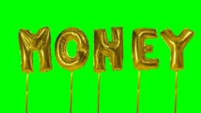 Dinero de la palabra de las letras de oro del globo del helio que flotan en la pantalla verde - almacen de video