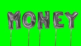 Dinero de la palabra de las letras de plata del globo del helio que flotan en la pantalla verde - almacen de video