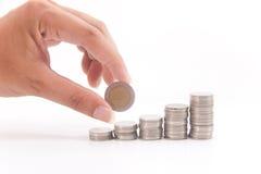Dinero de la pila y una mano en la acción Fotografía de archivo libre de regalías