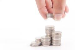 Dinero de la pila y una mano en la acción Foto de archivo libre de regalías