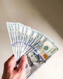 Dinero de las finanzas Primer de la mano que lleva a cabo d?lares fotos de archivo