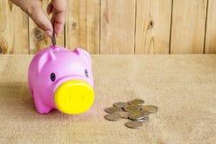 Dinero de los ahorros con la mano que pone la moneda en la hucha Imagenes de archivo