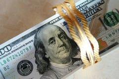 Dinero de los billetes de dólar con oro Foto de archivo libre de regalías