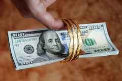 Dinero de los billetes de dólar con oro Imágenes de archivo libres de regalías