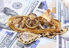 Dinero de los billetes de dólar con oro Fotos de archivo