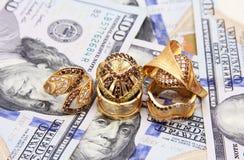 Dinero de los billetes de dólar con oro Fotos de archivo libres de regalías