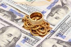 Dinero de los billetes de dólar con oro Imagen de archivo libre de regalías