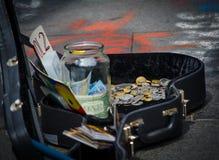 Dinero de los músicos de la calle en diversas monedas en la caja de la guitarra imagen de archivo