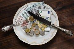Dinero de los países diferentes en la placa Imagen de archivo libre de regalías