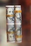 Dinero de los rollos de los billetes de dólar con la cadena del oro Fotos de archivo libres de regalías