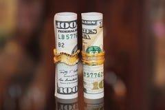 Dinero de los rollos de los billetes de dólar con los anillos de la joyería del oro Imagenes de archivo