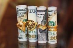 Dinero de los rollos de los billetes de dólar con los anillos de la joyería del oro Imagen de archivo