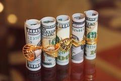 Dinero de los rollos de los billetes de dólar con los anillos de la joyería del oro Fotografía de archivo libre de regalías