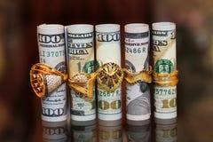 Dinero de los rollos de los billetes de dólar con los anillos de la joyería del oro Imagen de archivo libre de regalías