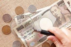 Dinero de los Yenes de Japón con la lupa Imagen de archivo libre de regalías