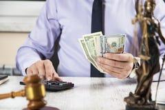 Dinero de mano con el juez y la calculadora foto de archivo libre de regalías