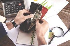 Dinero de mano del hombre con la cartera y la calculadora fotos de archivo