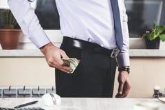 Dinero de mano del hombre en el bolsillo imagen de archivo