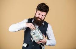 Dinero de ocultaci?n para uso futuro Hombre barbudo que invierte el dinero del tarro de cristal para los beneficios futuros Hombr fotos de archivo libres de regalías